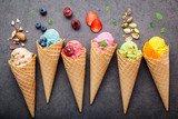 Various of ice cream flavor in cones blueberry ,strawberry ,pistachio ,almond ,orange and cherry setup on dark stone background . Summer and Sweet menu concept. - 199405474