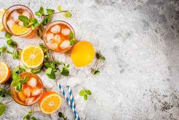 Cold summer drink. iced tea with lemon and mint, on grey stone background. Copy space top view