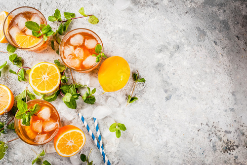 Cold summer drink. iced tea with lemon and mint, on grey stone background.  Copy space top view - 199426420