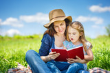Mother and daughter enjoy reading book sitting on green meadow in the summer park - 199429681