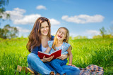 Mother and daughter enjoy reading book sitting on green meadow in the summer park - 199429812