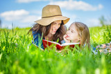 Mother and daughter lying on green grass enjoy reading book - 199429831