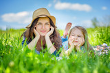 Mother and daughter lying on green grass enjoy summer day - 199429883
