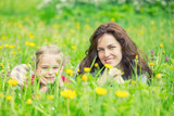 Mother and daughter lying on green summer grass with blooming yellow flowers - 199430076