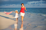 Mother and little daughter walking on the beach - 199430219