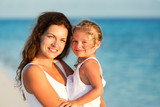 Portrait of happy mother and little daughter on sunny beach - 199430289