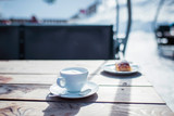 Cup of coffee with saucer on wooden outdoor table in wintersport area.