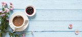 Coffee cup, jam and pink flowers on a pastel blue wooden background with copy space, top view from above, panoramic banner format - 199451898