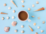 Many different sea shells on a blue background. Flat lay. Cup of coffee in the center - 199456644