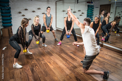 Leinwanddruck Bild Fitness instructor giving instructions to sporty people with weights in squat position.