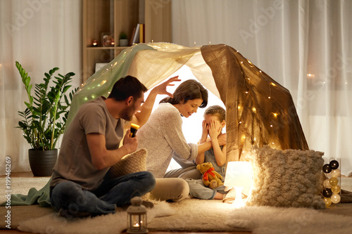 hygge and people concept - father with torch light telling scary stories to his daughter and wife, family having fun in kids tent at night at home