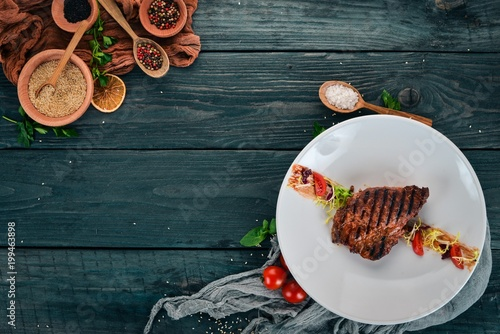 Foto op Plexiglas Steakhouse Juicy steak cooked on a grill. Top view. On a wooden background. Copy space.