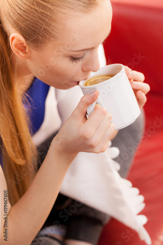 Woman lying on sofa under blanket drinking tea - 199467605