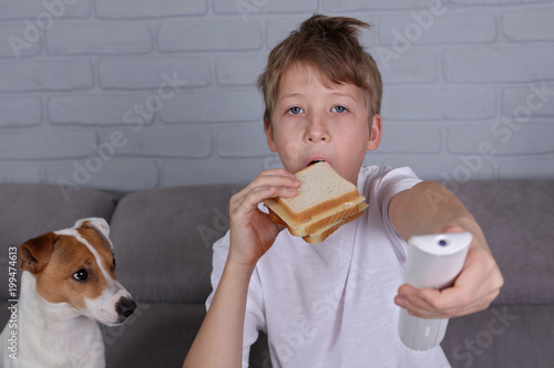 Foto Murales Children bad eating habits, Kid eating unhealthy junk food sandwich and watching TV