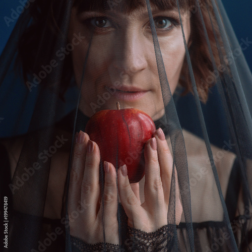 Beautiful woman witch with poison red apple