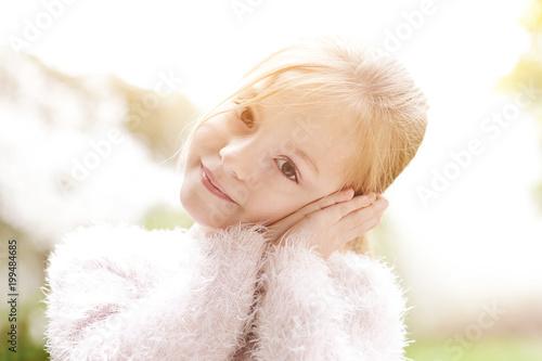 douce fillette blonde dans jardin au printemps