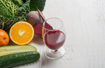Orange, cucumber, beet and borecole with fresh juice in glass