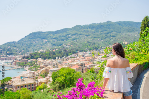 Fotobehang Liguria Back view of young woman background stunning town. Tourist looking at scenic view of Rapallo, Cinque Terre, Liguria, Italy