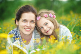 Mother and daughter lying on spring meadow enjoy reading book - 199498839