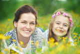 Mother and daughter lying on meadow enjoy spring flowers - 199498855