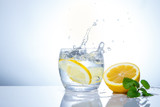 yellow lemons in a glass and splashes of water. Tasty and healthy food. Seasonal drinks