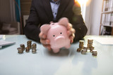 Businessperson's Hand Shaking Piggy Bank