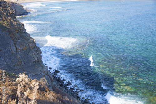 Mighty rock, collapses in a blue sea, with sun glare, majestic rocks © Юлия Моисеенко