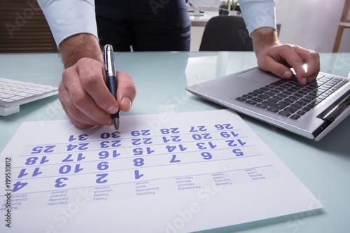 Businessperson Marking With Pen On Calendar