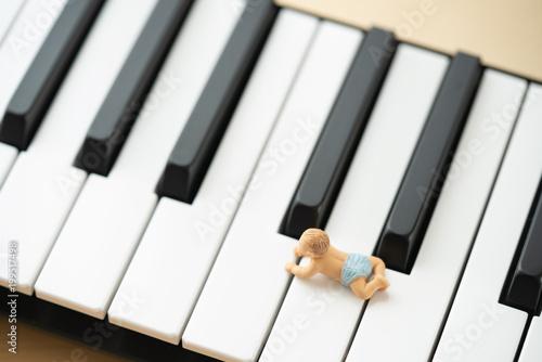 鍵盤の上に乗る赤ちゃんの人形 - 199517498