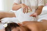 Masseuse pour oil on the hand and young asian woman relaxing receiving back massage at spa salon