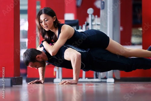 Exercises with weighting. Young male athlete doing push-ups with young athletic Asian lying on it in the gym