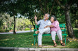 healthy senior couple relaxing  seats on Chair in the park
