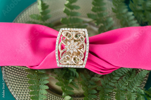 Pink napkin with a patterned clip. table setting. Wedding decor in the magic forest for a loving couple. Pink and green colors. - 199536461