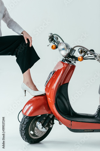 Close-up view of woman wearing white heel shoes posing by red scooter