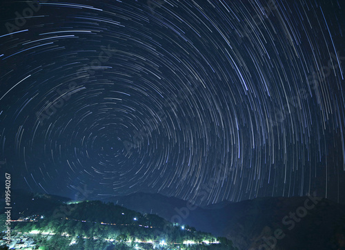 Fotobehang Nachtblauw McLeod Ganj at night with star trails in sky above mountains, India