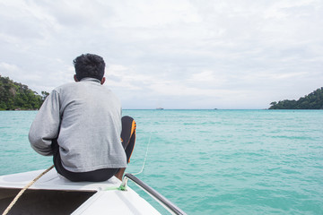 Man sits on a boat front while crossing Andaman.