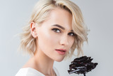 portrait of attractive blonde girl with black rose, isolated on grey - 199544054