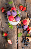 Ice cream, Blueberry and Raspberry scoop in cone on wooden table.   - 199546673