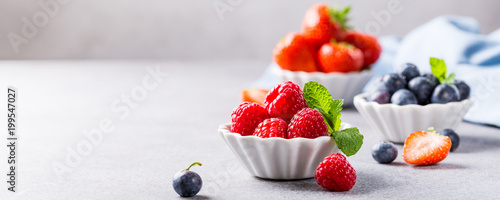 White ceramic bowl with fresh healthy berries. Raspberry, strawberry and blueberries. Copy space. Banner. - 199547027
