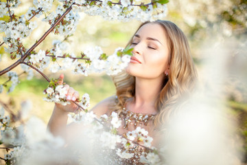 Spring. Close-up horyzontal portrait of a beautiful girl inhaling aroma of blooming tree in garden. Artwork. Copy space. Sotf focus