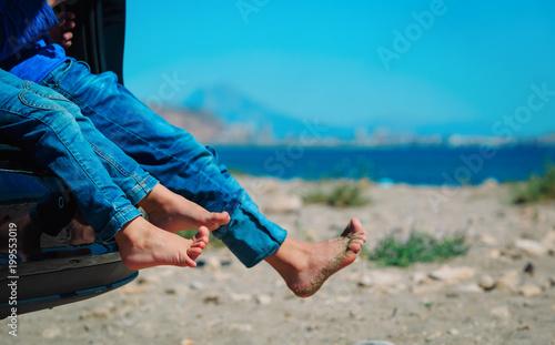 feet of happy kids travel by car on beach
