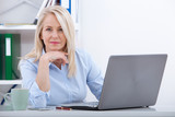 Beautiful business lady is looking at camera and smiling while working in office - 199559049