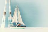 nautical concept with white decorative sail boat and wooden oars over blue background.