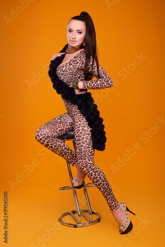 Fototapeta Sexy woman wearing leopard suit on orange background