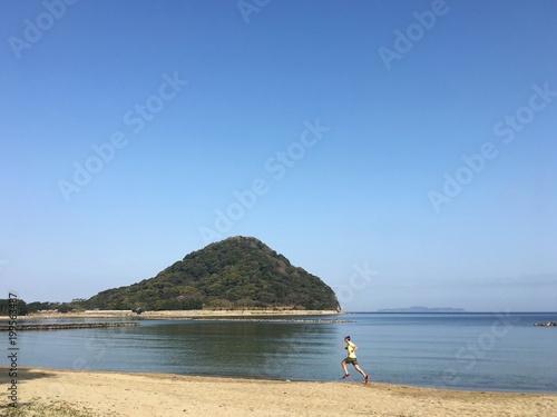 Zdjęcia na płótnie, fototapety, obrazy : Man running on sandy beach with blue sky background