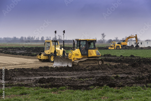 Fotobehang Trekker Excavators and bulldozers preparing the ground for the construction of a factory