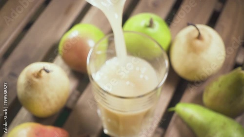 The camera focuses on pear juice pouring into a glass on a wooden table slow motion