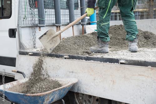 Arbeiter schaufelt Kies von einer Ladefläche