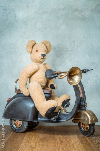 Fotobehang Scooter Teddy Bear sitting on old black retro toy scooter with classic klaxon in front concrete textured wall background. Vintage style filtered photo