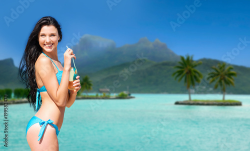 summer holidays, vacation and beach concept - smiling woman in bikini with bottle of non alcoholic drink over bora bora island beach background